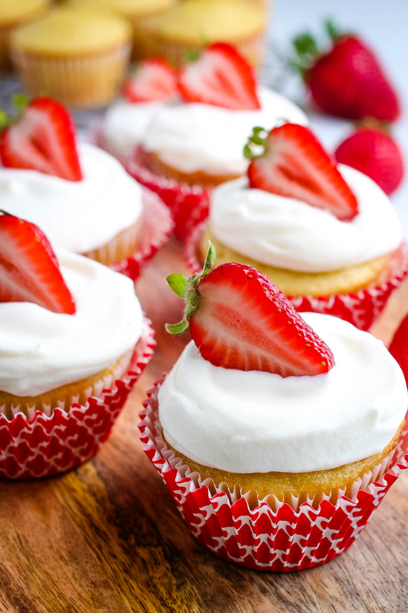 strawberry topped strawberry shortcake cupcakes with whipped cream frosting, in red cupcake liners, on wooden cutting board
