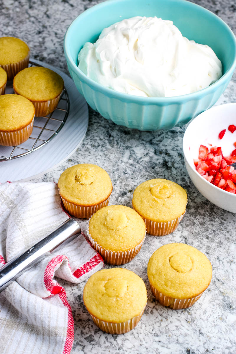 strawberry stuffed cupcakes with red and white kitchen towel and apple corer on granite countertop with light blue bowl of whipped cream frosting