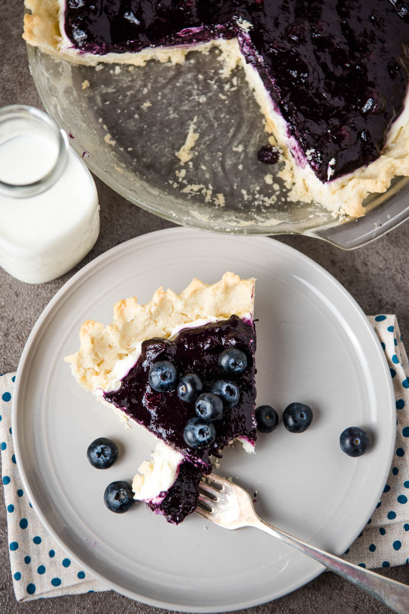 blueberry cream pie sliced and served on gray plate with fresh blueberries and a fork, along with a jar of milk