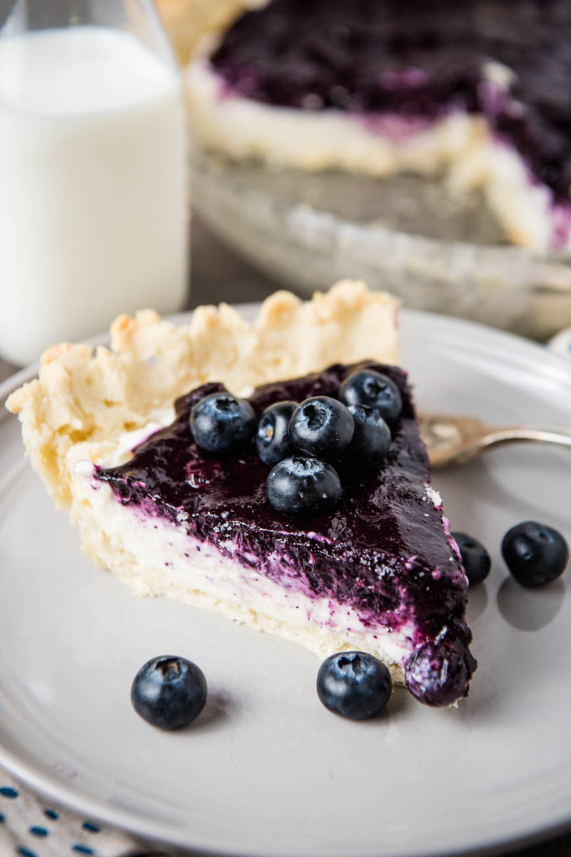 whole slice of cream cheese blueberry pie on gray plate with fork, fresh blueberries, and jar of milk