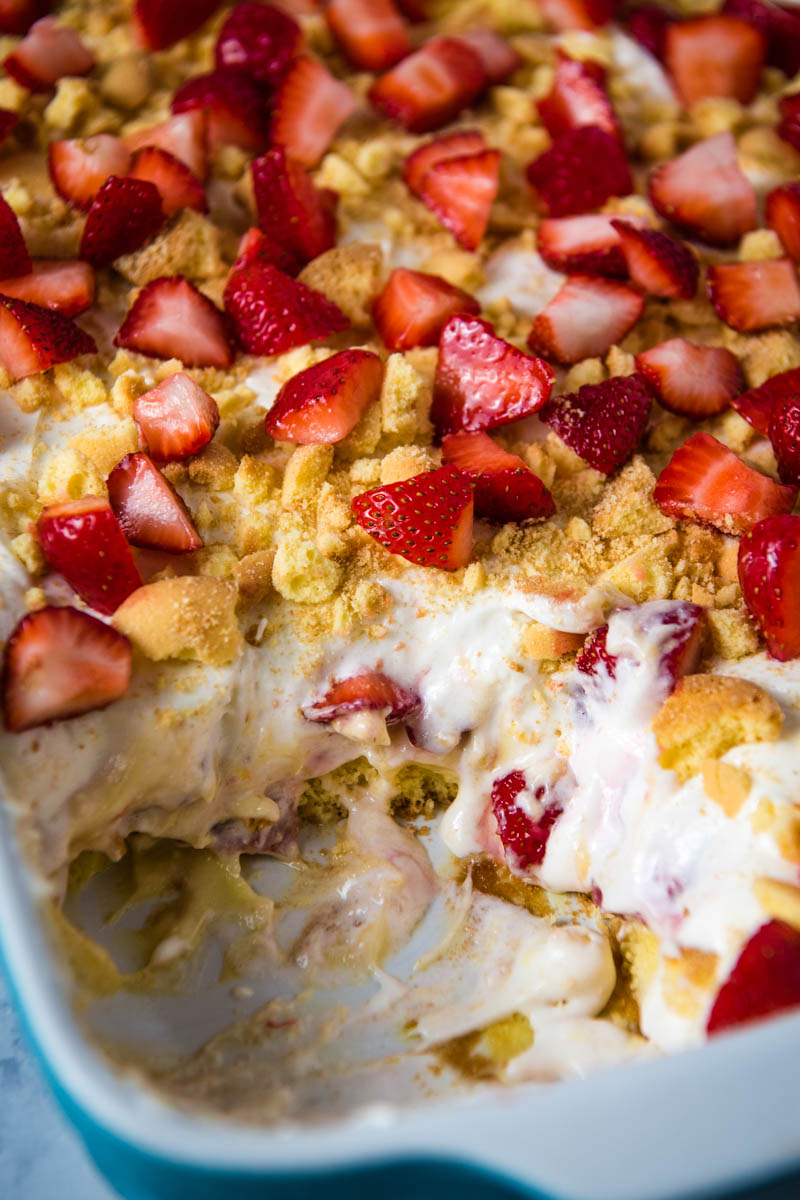 strawberry delight with vanilla pudding scooped out of blue baking dish