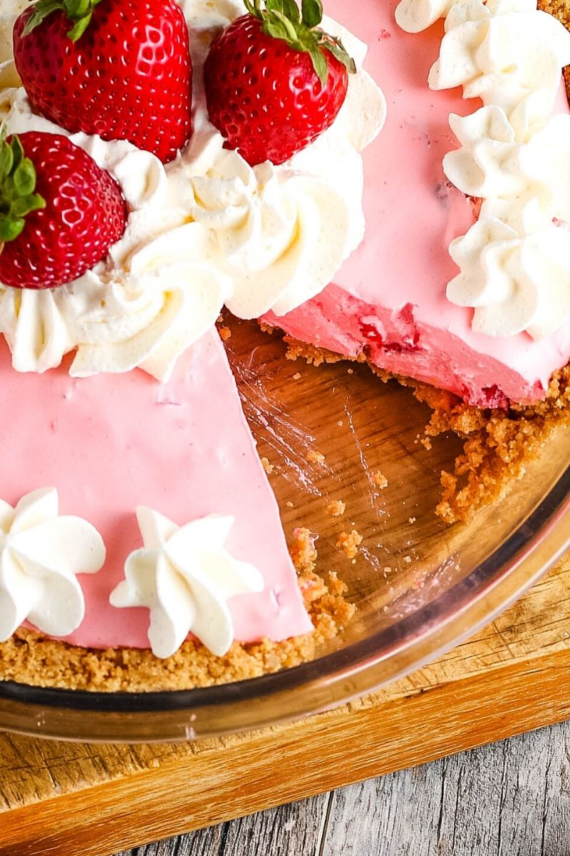 sliced strawberry Jello pie in pie plate, decorated with whipped cream and fresh strawberries