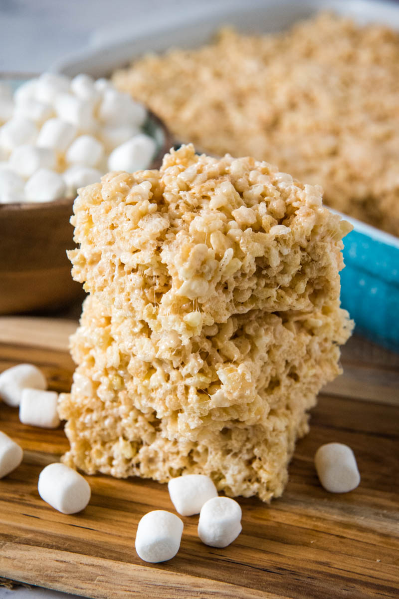 stack of microwave Rice Krispie squares on wooden cutting board with mini marshmallows