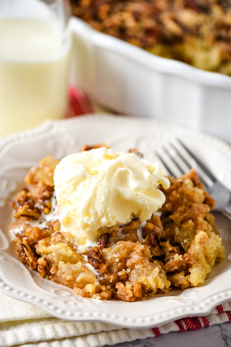 serving of caramel apple dump cake topped with scoop of vanilla ice cream on white plate with fork