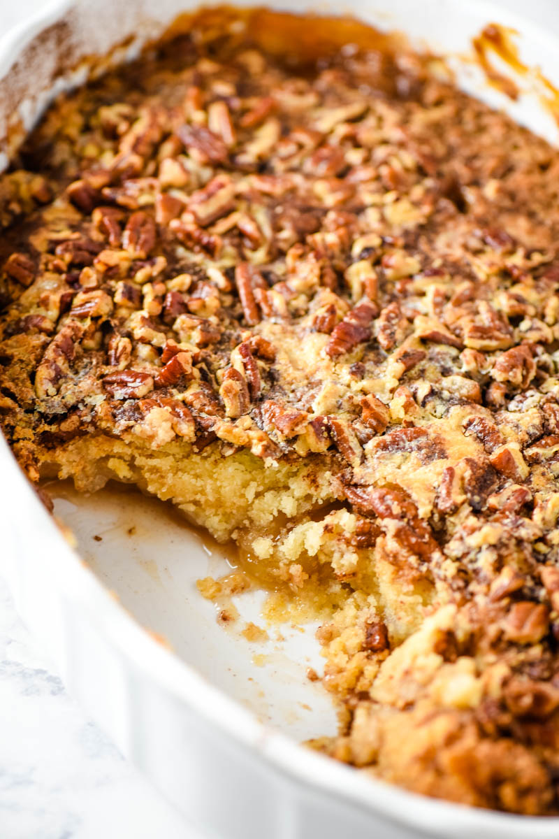 baked and scooped caramel apple dump cake with pecans in oval white baking dish