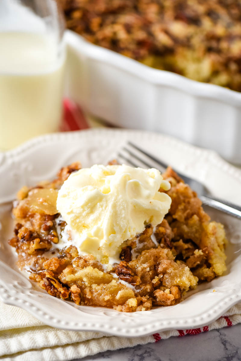 scoop of caramel apple pecan dump cake with vanilla ice cream on white plate with fork