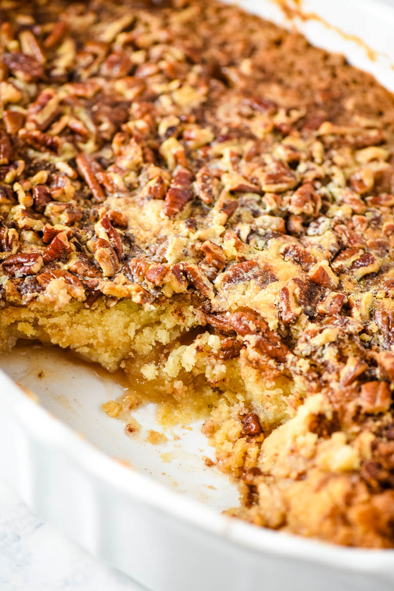 caramel apple pecan dump cake baked and scooped out of oval white baking dish