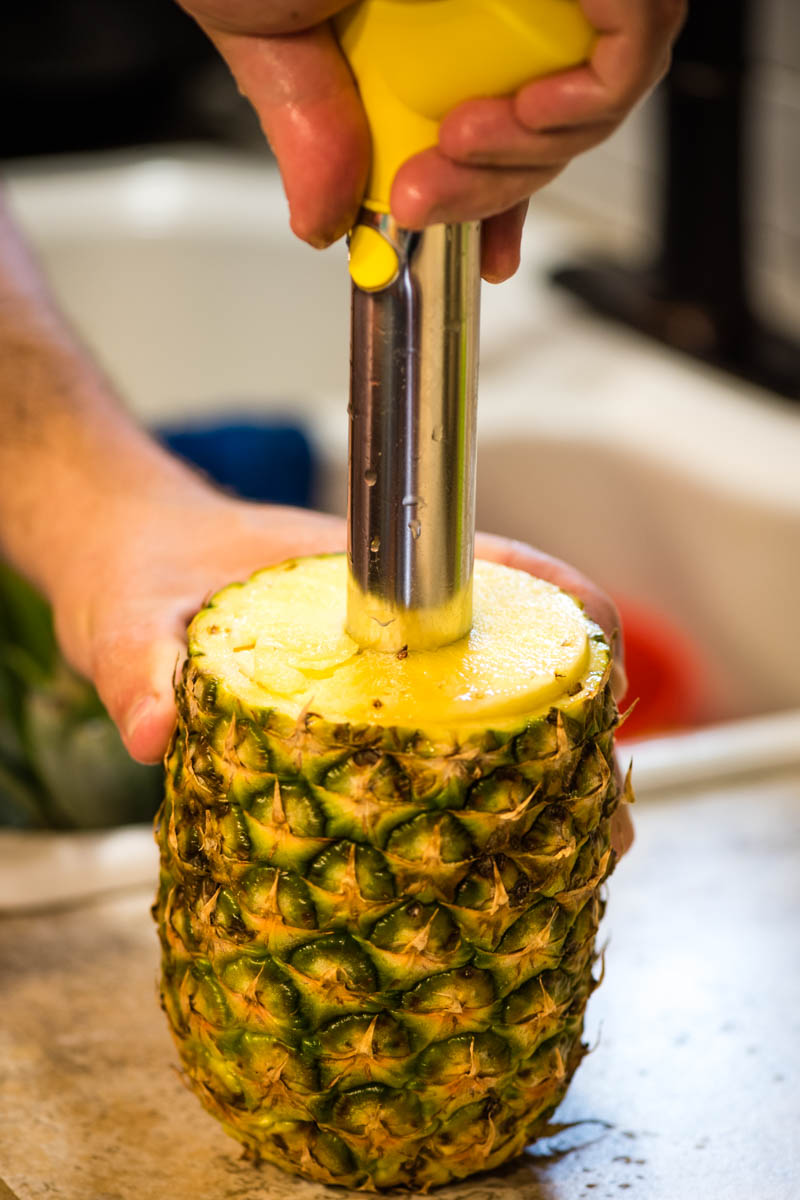 hands coring pineapple with pineapple corer