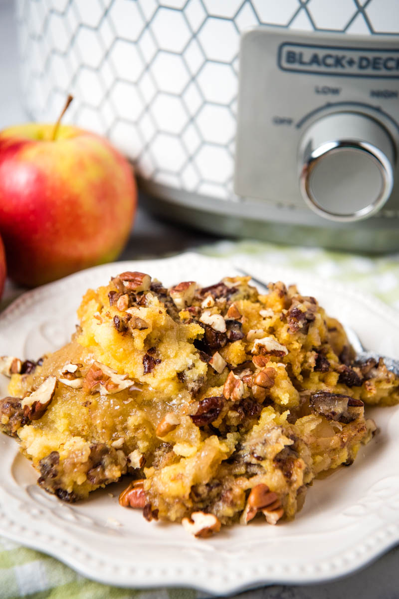 serving of Crock Pot apple dump cake on white plate with fork