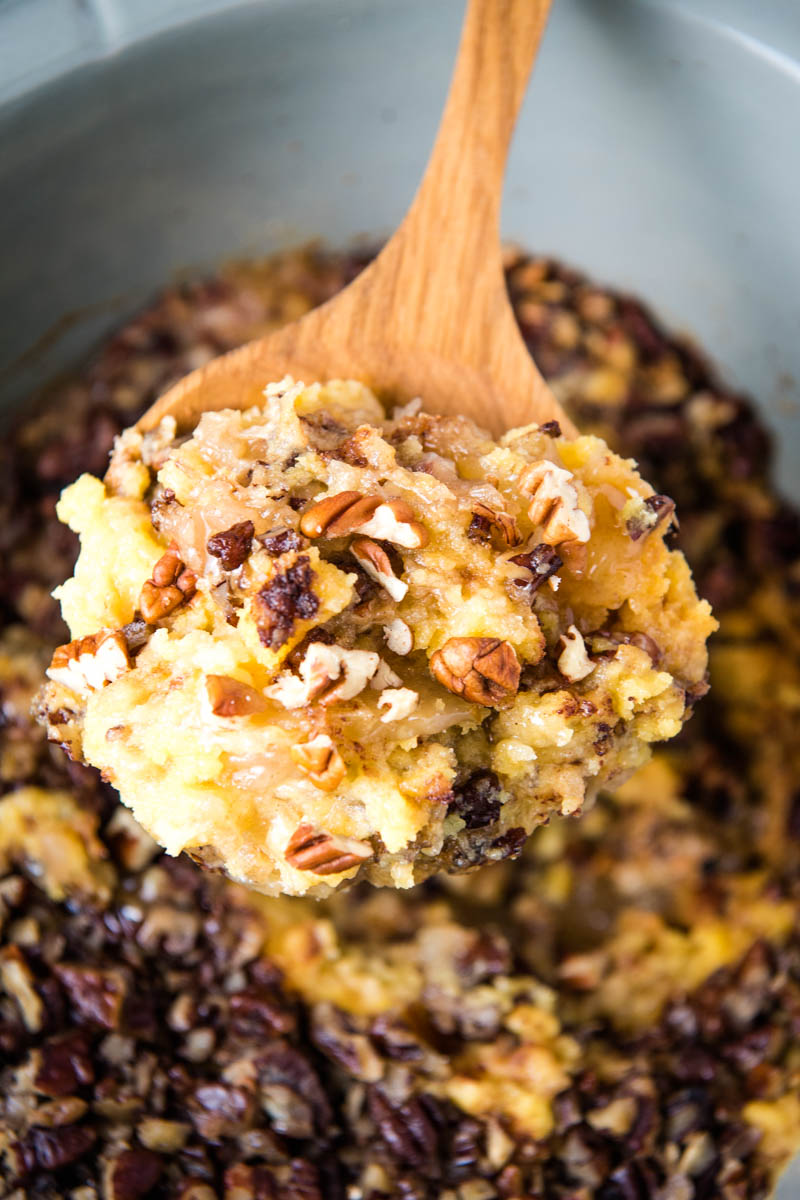 scooping CrockPot apple cobbler with cake mix out of gray slow cooker with wooden spoon