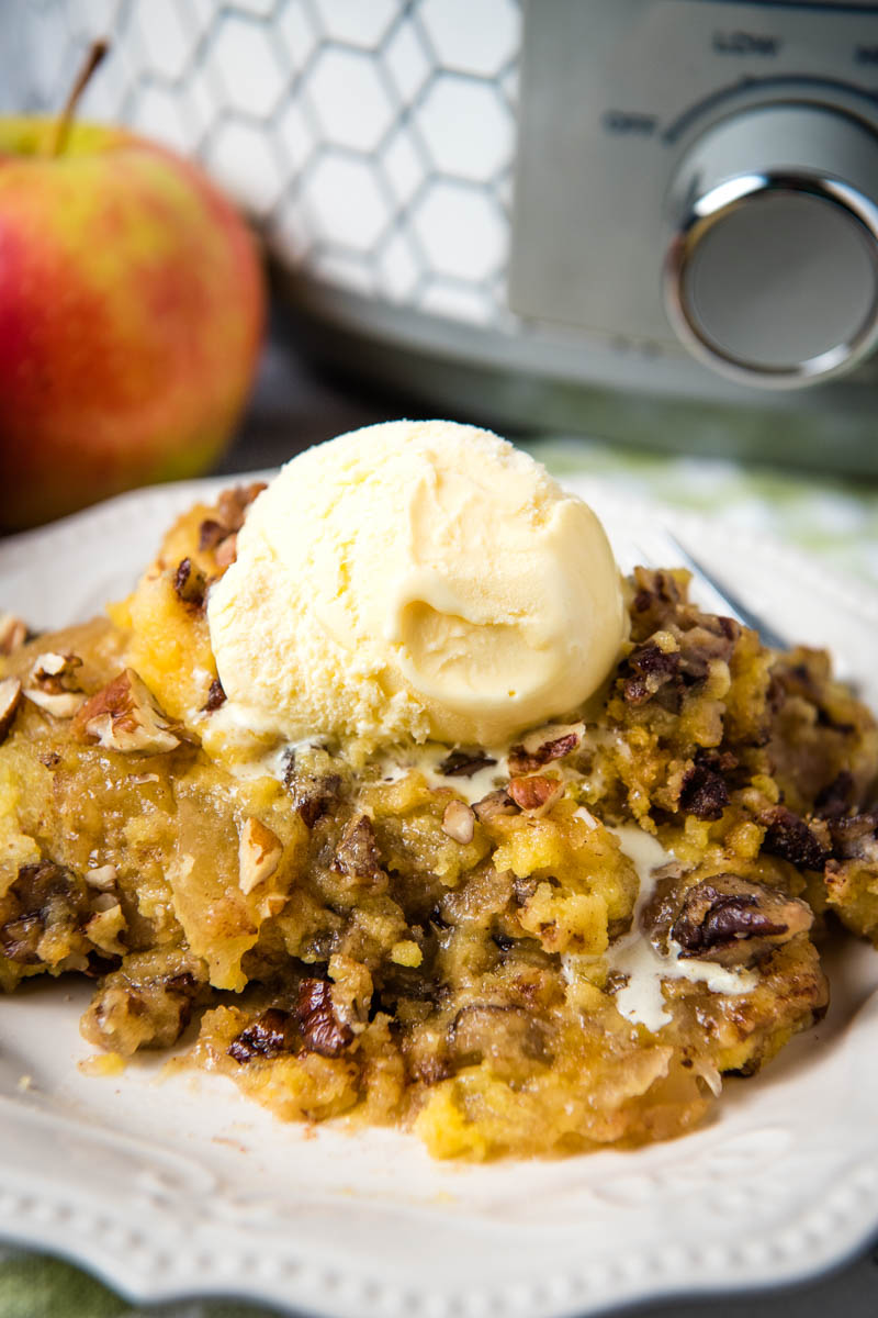 serving of slow cooker apple dump cake on white plate with melting scoop of vanilla ice cream on top