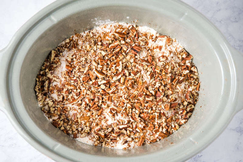 chopped pecans sprinkled over yellow cake mix in gray slow cooker
