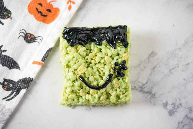 decorated green Rice Krispie treats with black icing for Frankenstein hair, smile, and stitches
