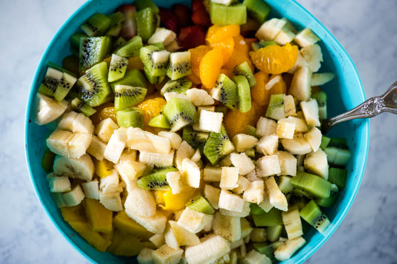 sugar added to tropical fruit salad in large blue mixing bowl