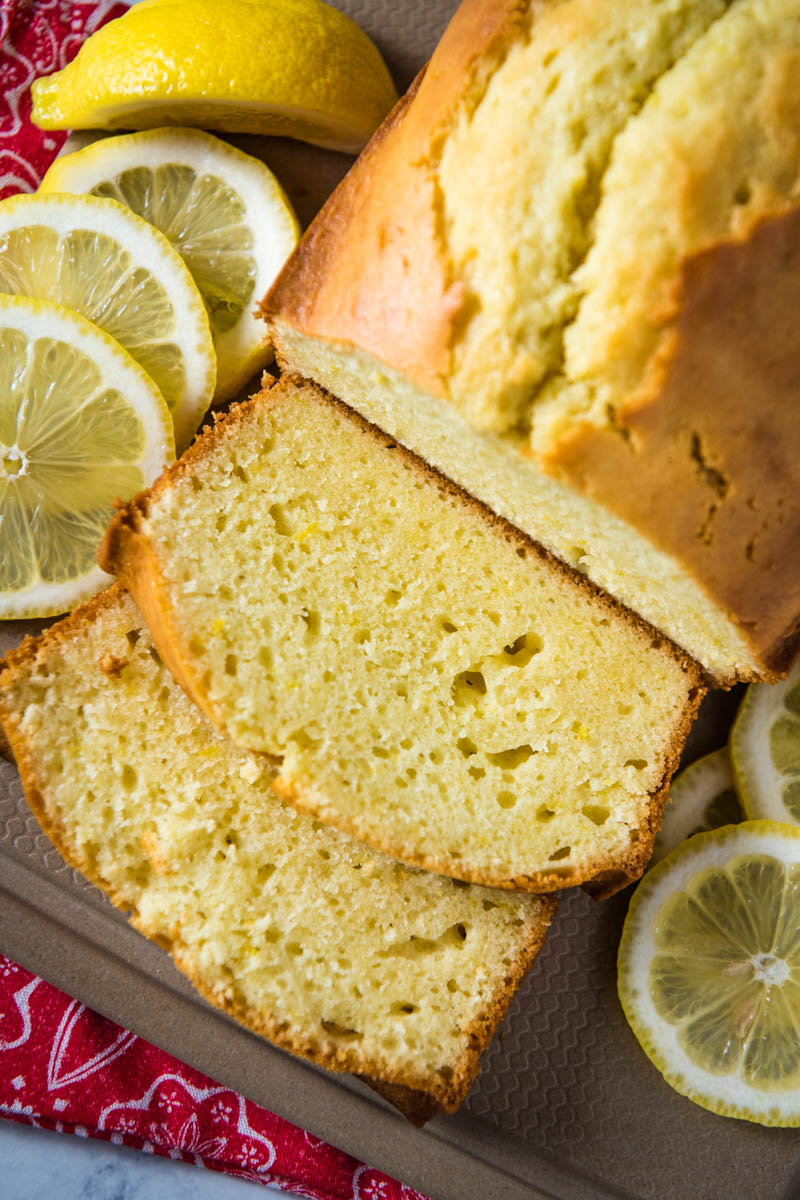 sliced loaf of gluten-free lemon pound cake on brown cutting board with lemon slices