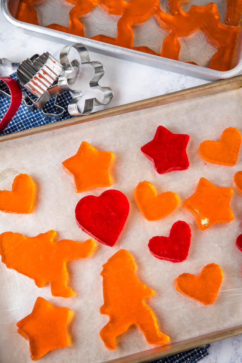 orange and cherry Jello Jigglers in heart, star, and Bigfoot shapes on baking sheet