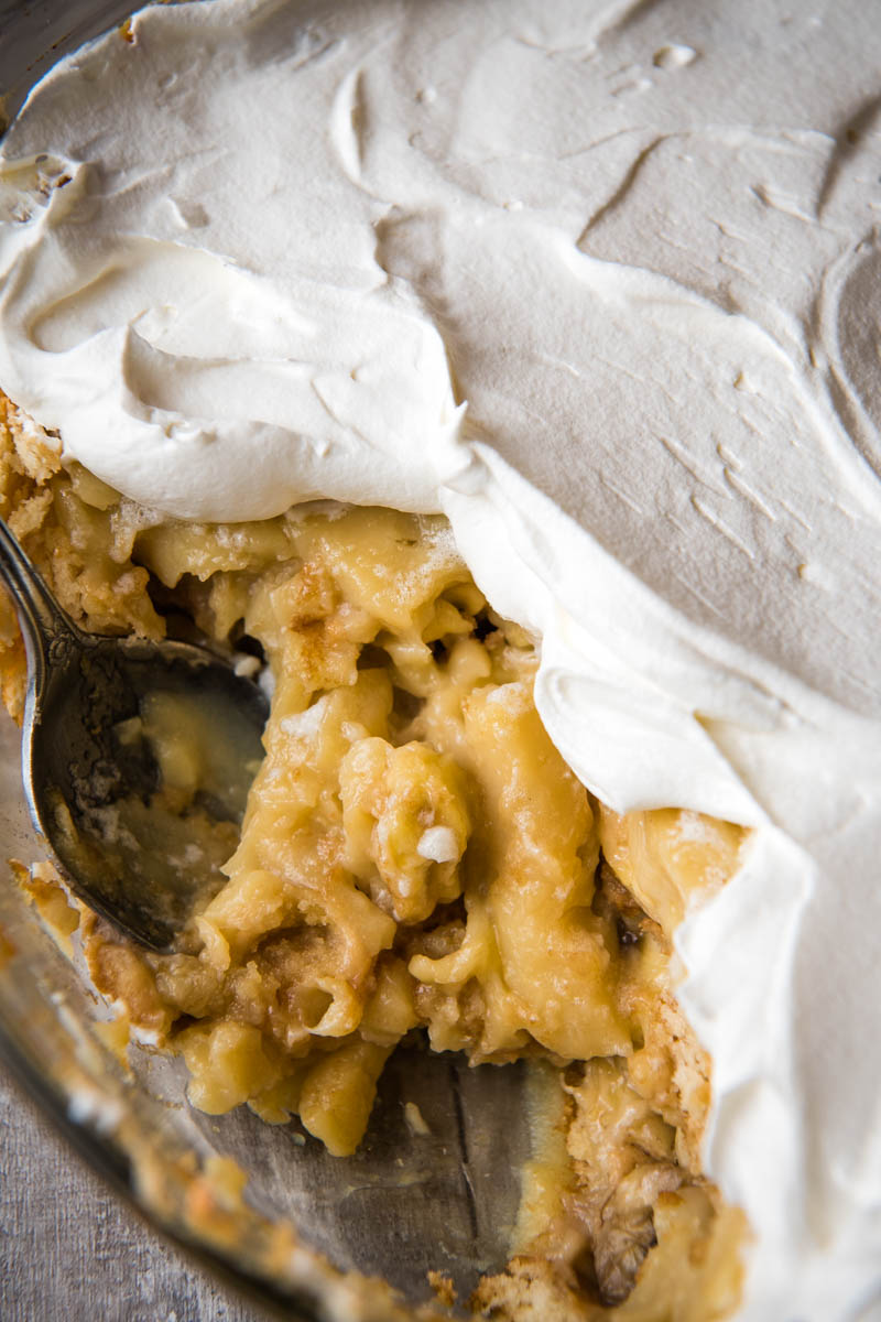 serving spoon in round casserole dish full of old-fashioned banana pudding topped with whipped cream