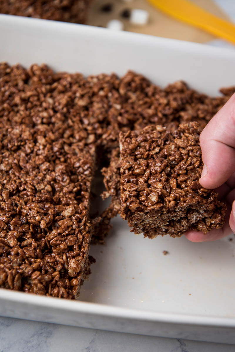 hand pulling no bake chocolate Rice Krispie squares from white baking dish