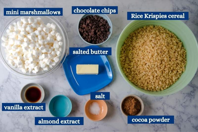ingredients for chocolate rice crispy treats on white marble countertop, including mini marshmallows, chocolate chips, Rice Krispies cereal, salted butter, vanilla extract, almond extract, salt, and cocoa powder