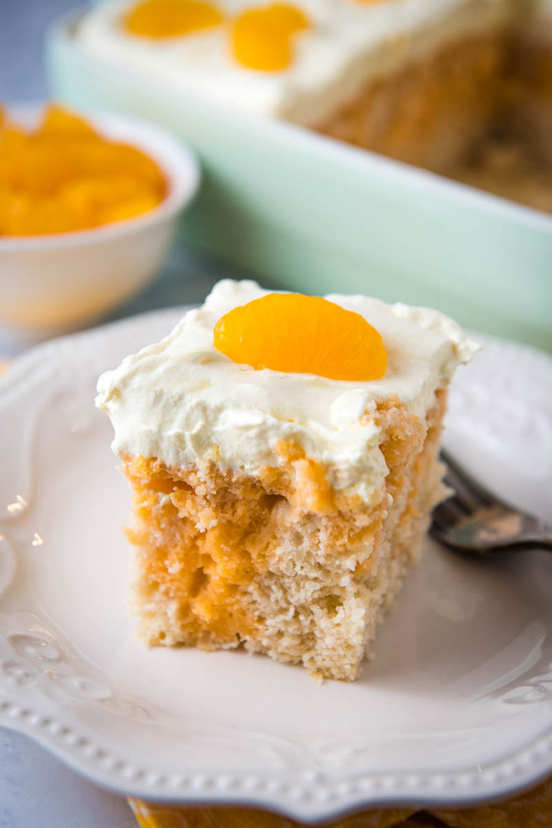 slice of orange poke cake with whipped frosting and mandarin orange on top, on ivory plate with fork